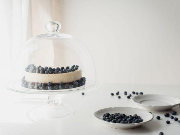 Boleira de vidro com bolo de frutas ao lado de pratos e frutas.