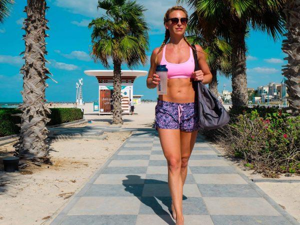 Na foto uma mulher em uma praia com top e shorts de academia segurando uma garrafa de água usando uma bolsa esportiva.