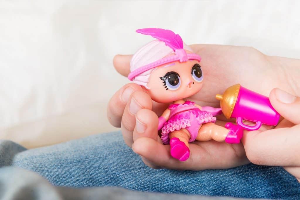 Pessoa dando mamadeira para boneca LOL.