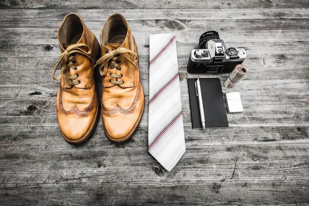 Imagem de botas ao lado de uma gravata, câmera fotográfica e alguns acessórios.
