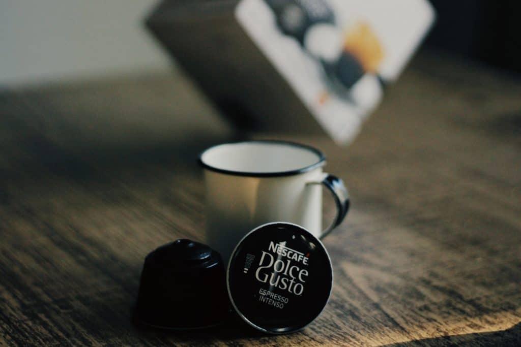 Imagem de uma xícara e duas cápsulas de café da Dolce Gusto.