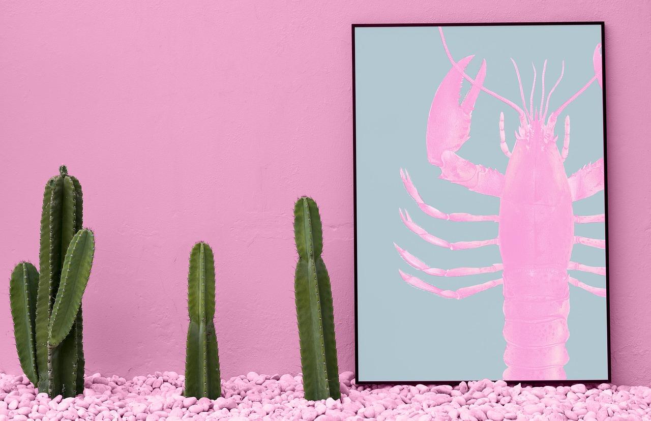 Imagem de placa decorativa com imagem de uma lagosta ao lado de cactos.