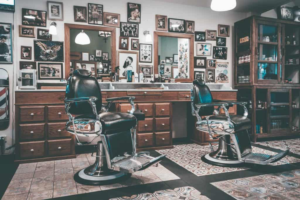 Duas cadeiras de barbeiro em barbearia.