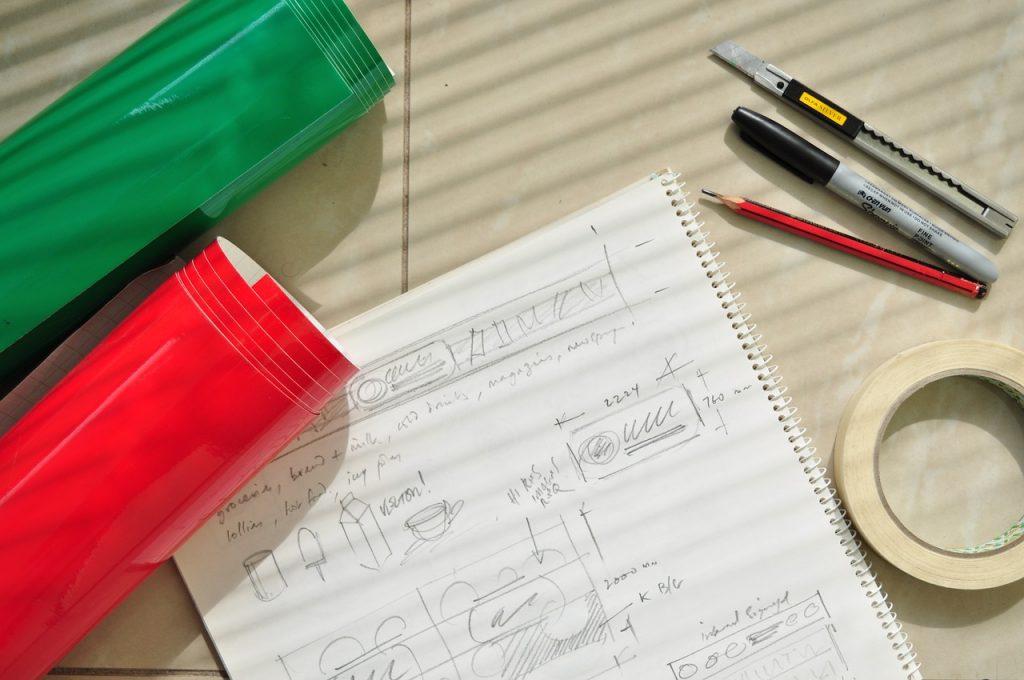Imagem mostra uma mesa com um caderno aberto, com a folha desenhada, ao centro. Ao seu redor, dois estojos, um lápis, uma caneta, um estilete e uma fita crepe.