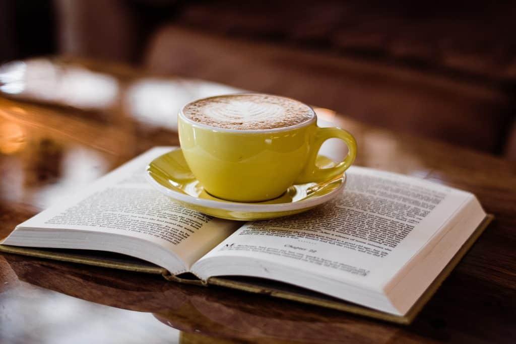 Uma xícara de café cheia está em cima de um livro mantendo-o aberto.