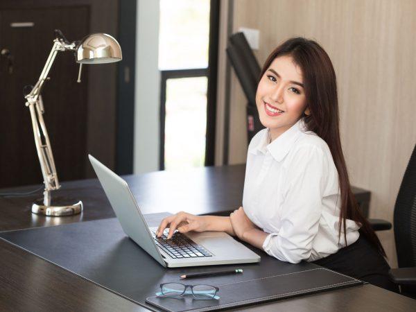 Na foto uma mulher em uma mesa de trabalho.