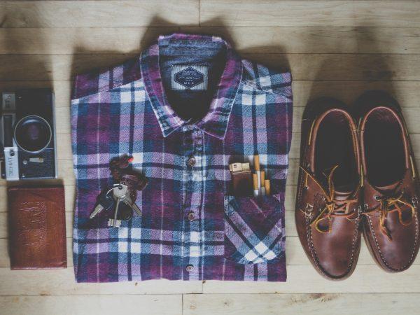 Imagem mostra uma camisa social masculina dobrada junto a outros acessórios.