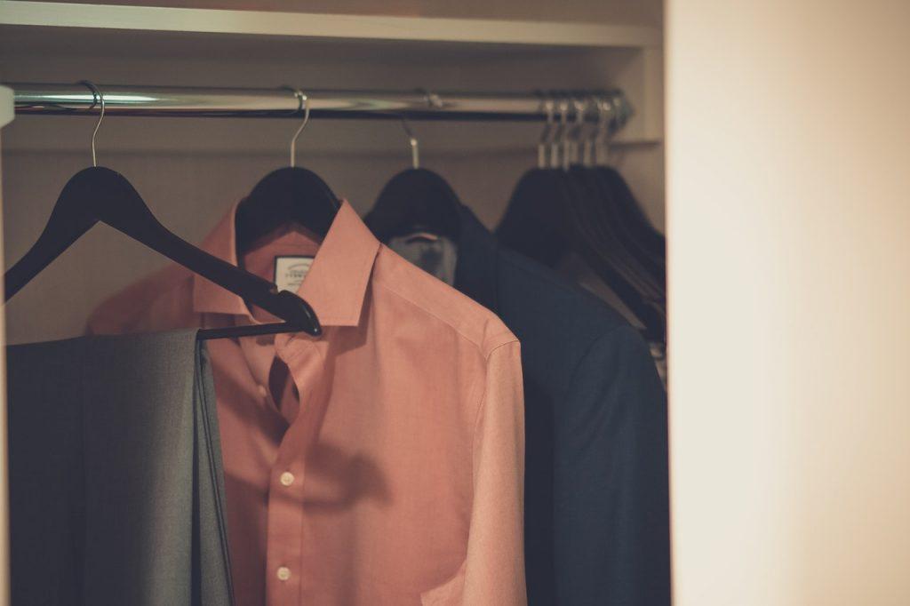 Imagem mostra camisas sociais penduradas em um guarda-roupa.