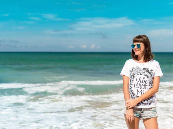 Imagem mostra uma mulher de costas para o mar, usando shorts jeans, camiseta branca e óculos escuros.