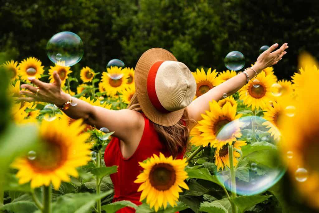 Imagem de uma mulher em um campo de girassóis.