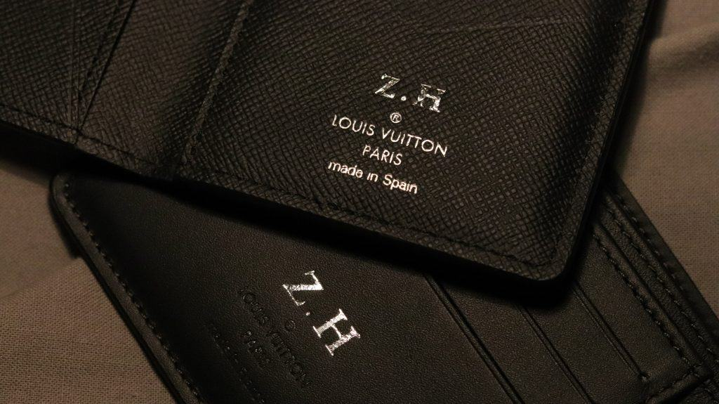 Imagem mostra o close de uma capa para passaporte da Louis Vuitton, que está apoiada sobre uma carteira da mesma marca.