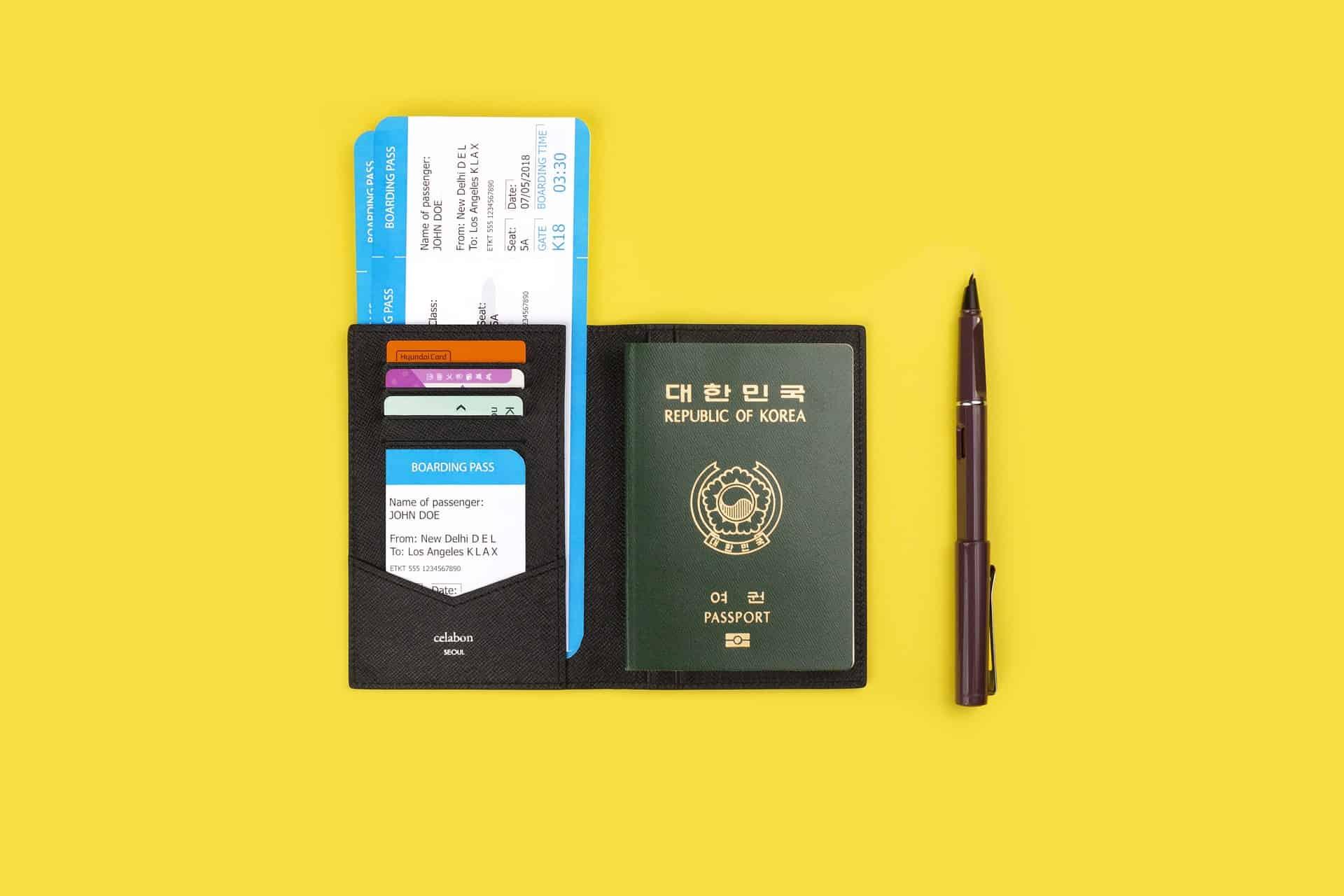 Imagem mostra uma carteira contendo um passaporte, uma passagem de avião e três cartões ao lado de uma caneta. Ambos sobre uma superfície amarela.