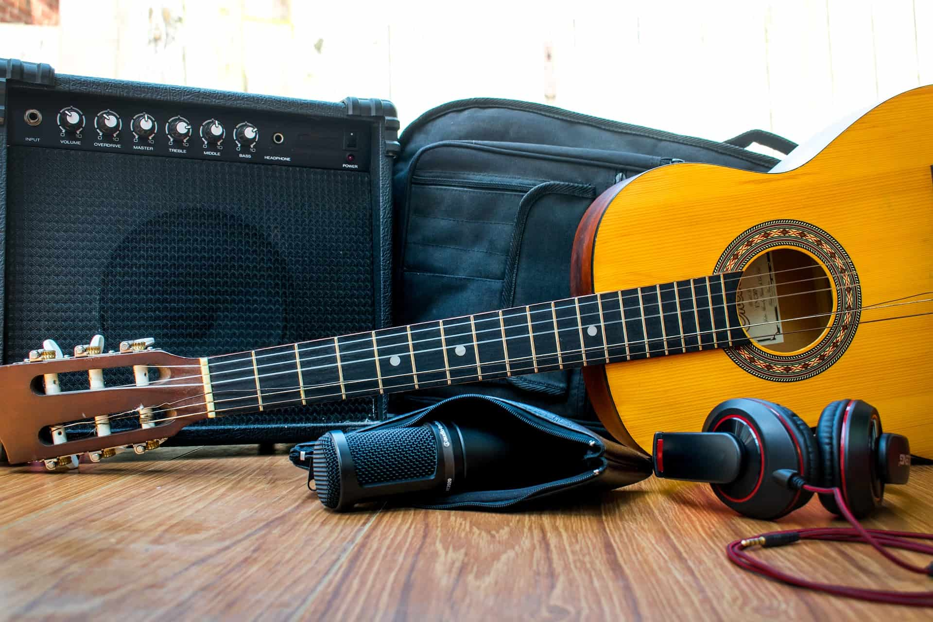 A guitar case next to an amplifier and behind a guitar.