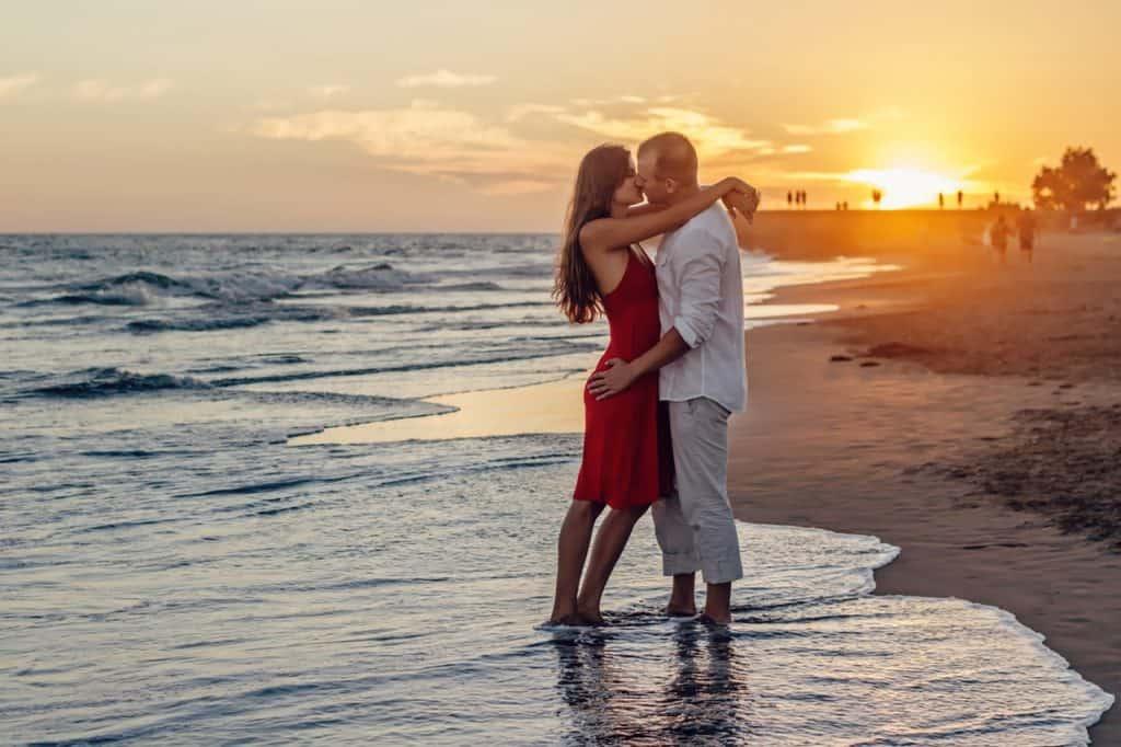 Imagem de um casal se beijando na praia.
