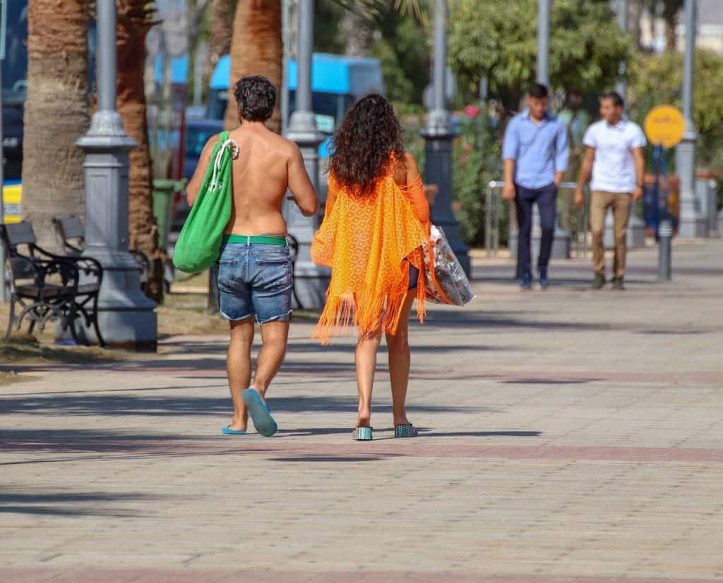 Homem de short e mulher de bata de renda laranja caminhando no calçadão da praia.