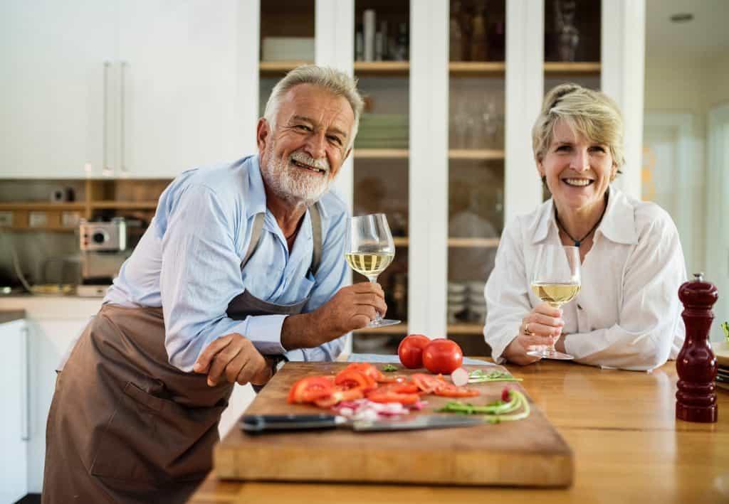 Casal maduro degusta taça de vinho branco em torno de grande tábua de corte em madeira com legumes diversos picados.