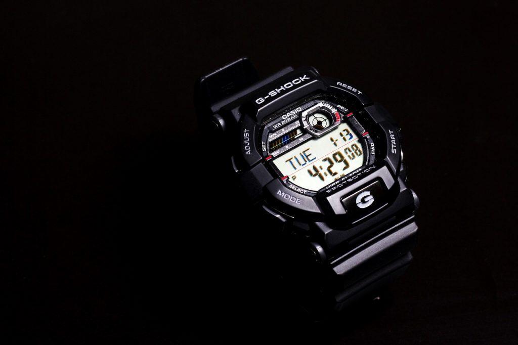 Imagem mostra um relógio Casio masculino, modelo G-Shock, sob um fundo preto. A hora apontada no relógio é 4:29.