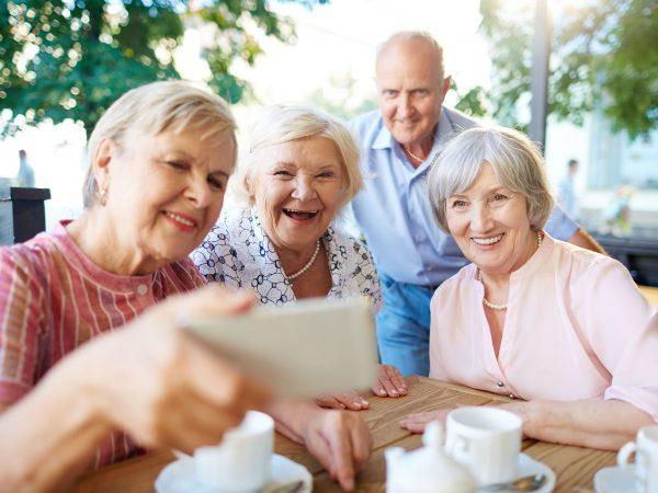 Imagem de um grupo de idosos tirando uma selfie.