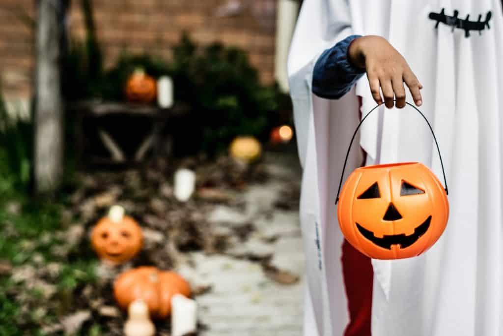 Na foto um menino vestido de fantasma segurando um potinho em formato de abóbora.