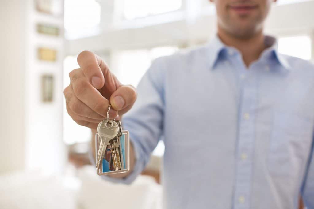 Imagem em close de uma mão de homem passando chave para outro homem em uma mesa de escritório.