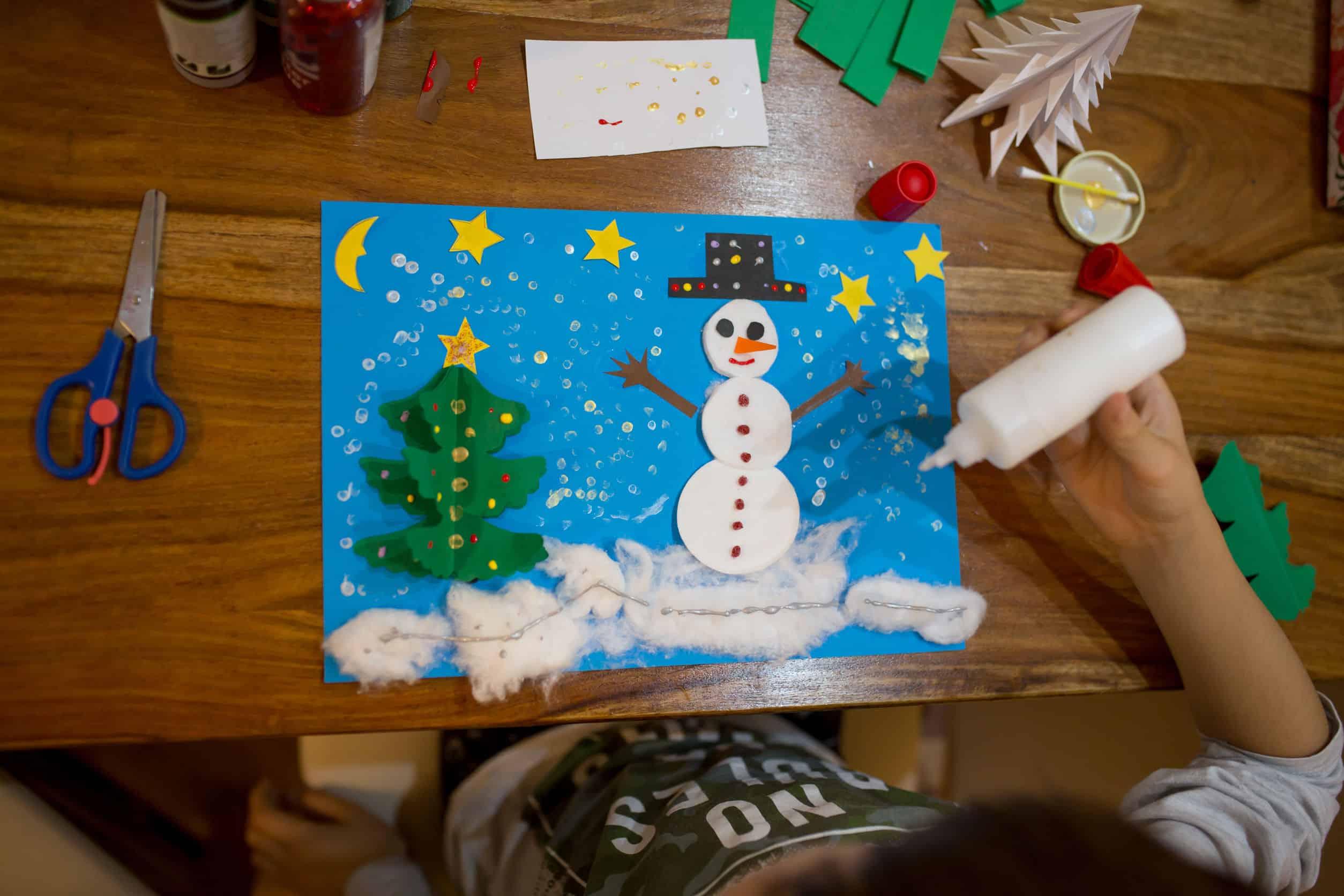 Criança dá acabamento de desenho com colagem com cola colorida.