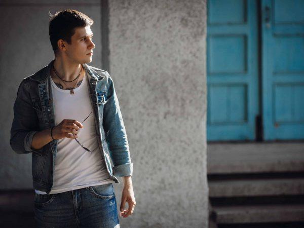 Imagem de homem olhando vestindo camiseta branca, calça jeans, jaqueta jeans, colar e pulseira, olhando para o lado com um óculos de sol na mão.