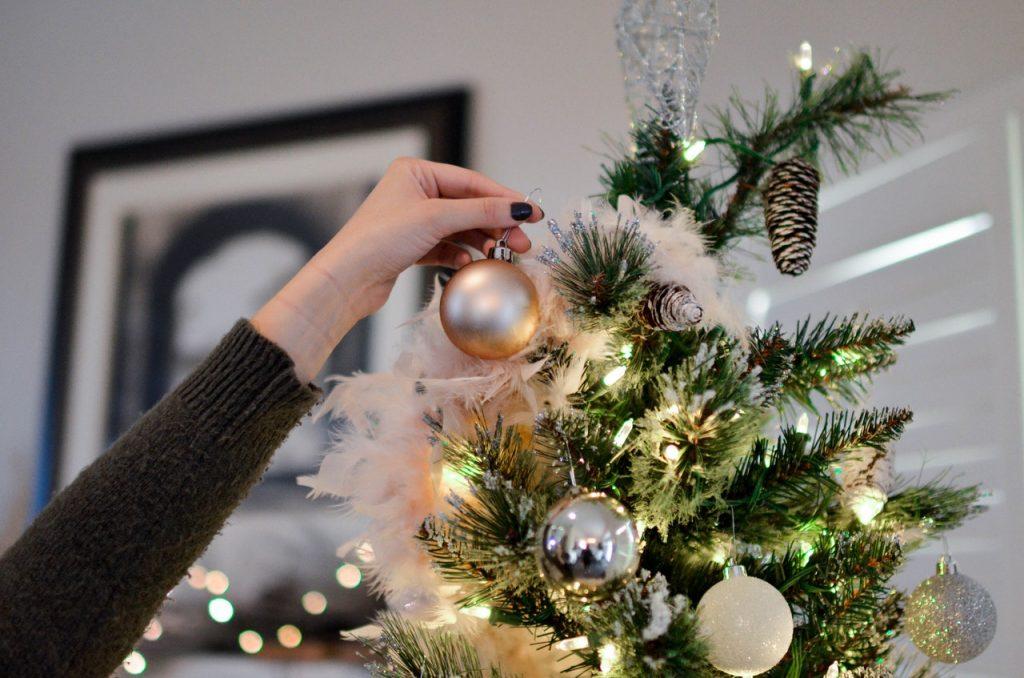Na foto vê-se a mão de uma mulher colocando uma bola de Natal dourada no topo de uma árvore de Natal.