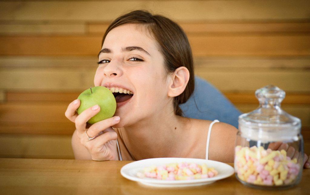 Moça morde maçã ao lado de pote com cereal matinal.