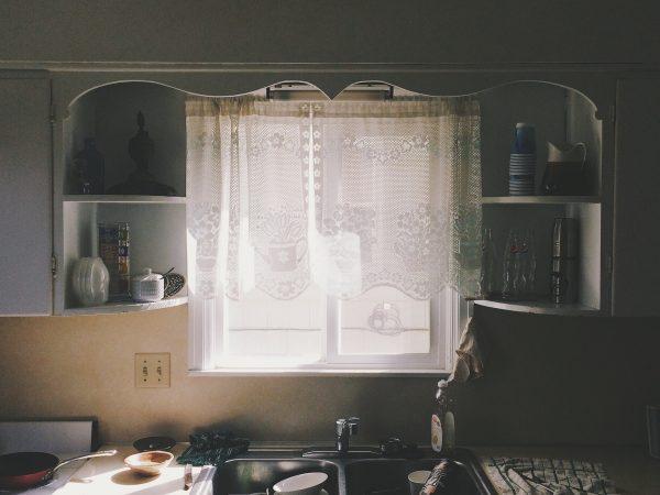 Imagem mostra cortina de cozinha branca com detalhes em renda instalada em janela acima da pia.