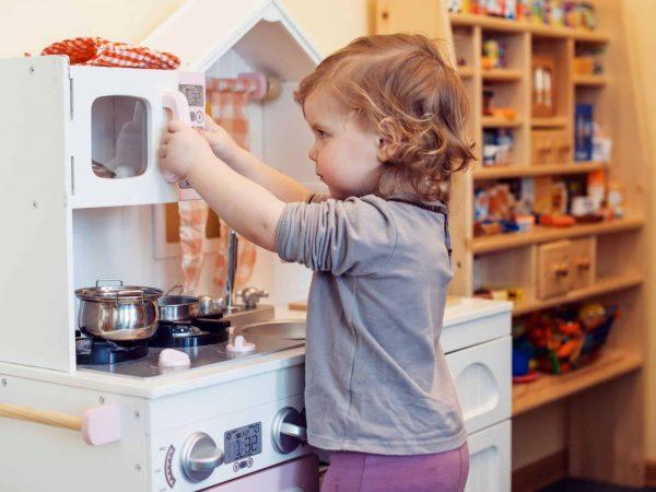 Criança brincando com cozinha de brinquedo.