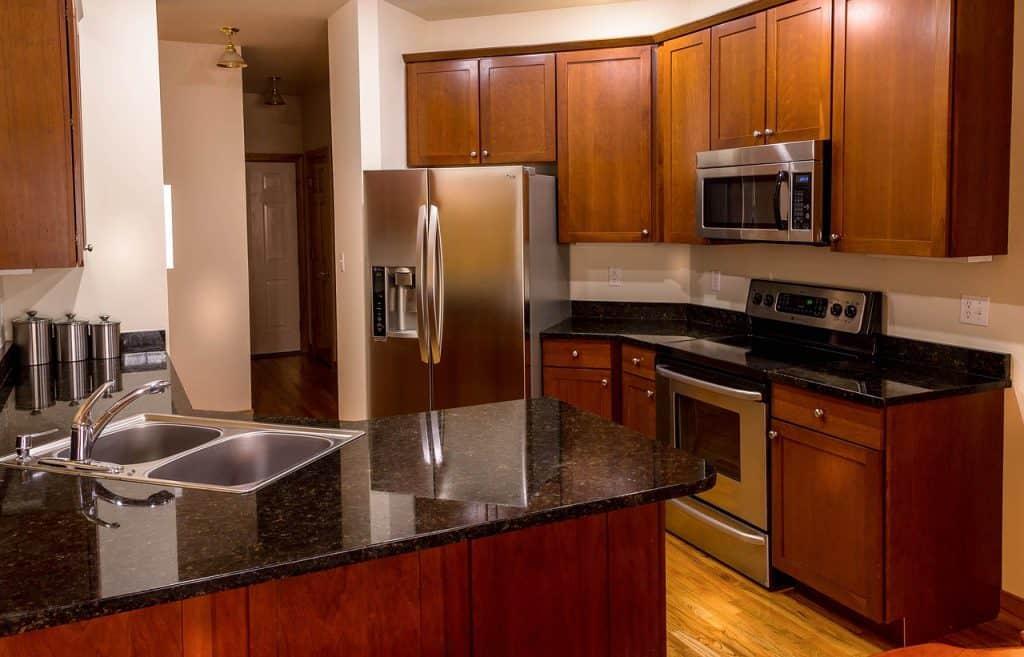 Cozinha em madeira marrom e preto, com geladeira do tipo Syde by Syde e dispenser de água na porta.