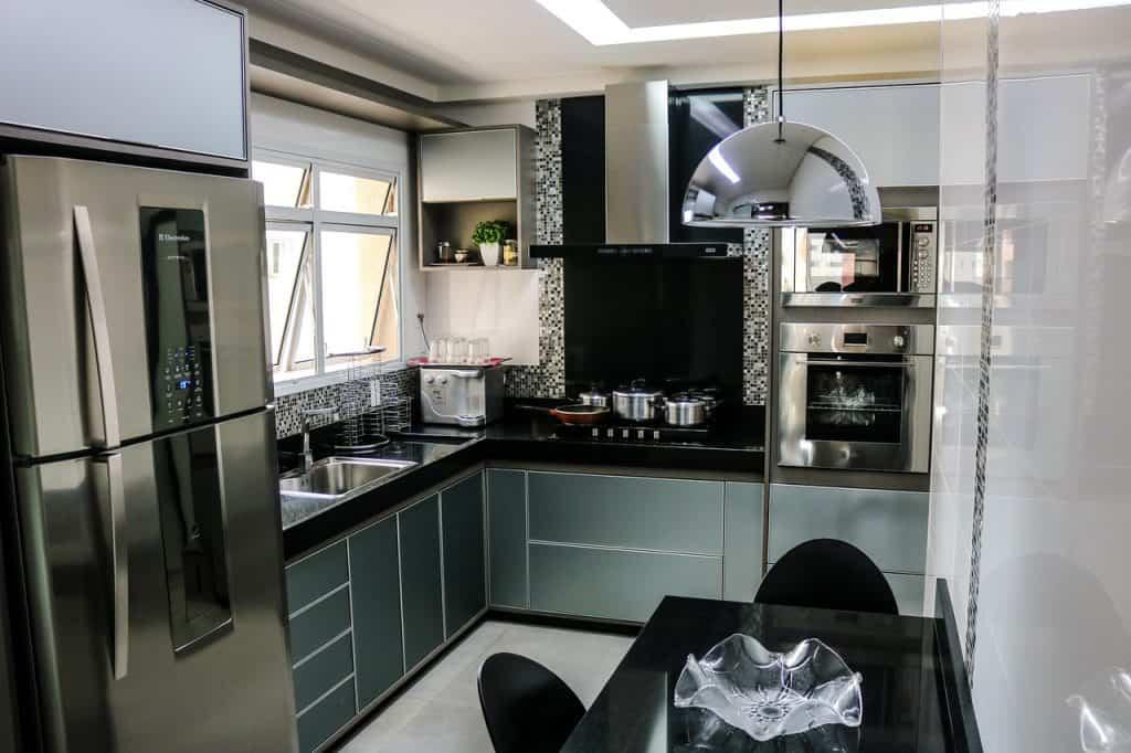 Cozinha preta e cinza, com geladeira de duas portas, na cor inox com freezer na parte de cima.