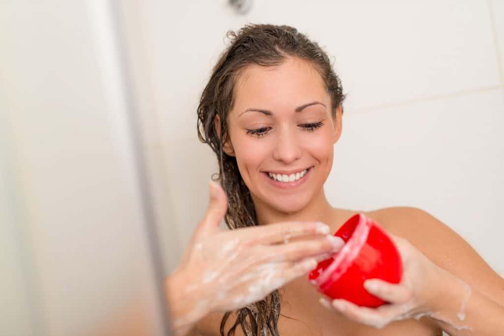 Foto de uma mulher sorrindo enquanto lava o cabelo. Ela segura um potinho vermelho com um creme branco dentro.