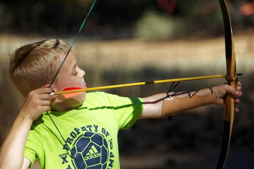 Menino usando arco e flecha.