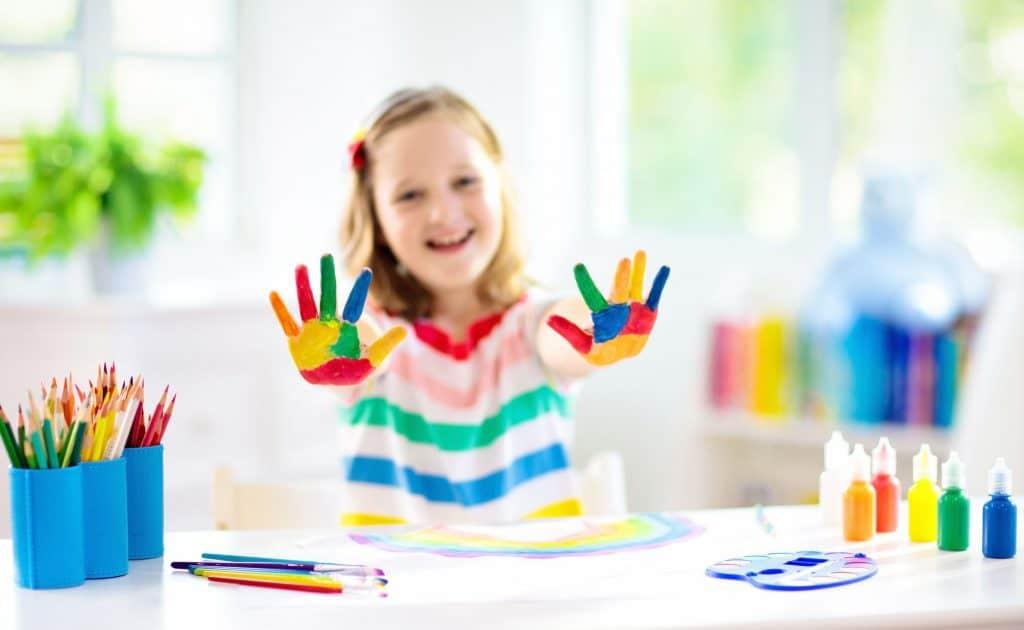 Menina sorri enquanto brinca com cola colorida.