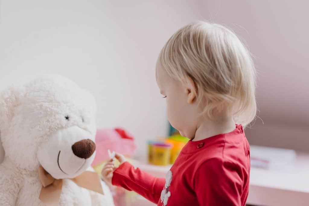 Bebê brincando com urso de pelúcia.