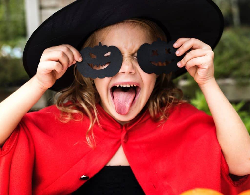 Na foto uma menina fantasia de bruxa mostrando a língua.