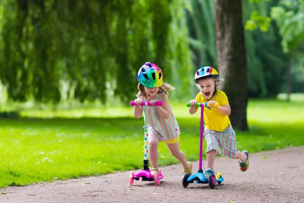 Menino e menina andando de patinete.