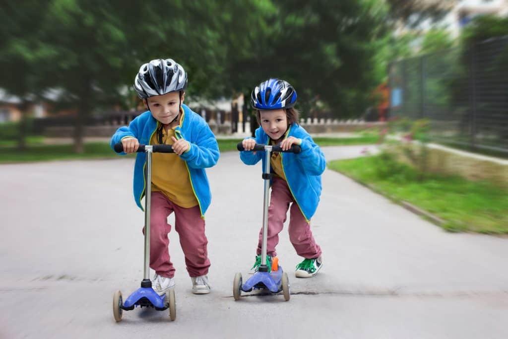 Duas crianças brincando com patinetes.