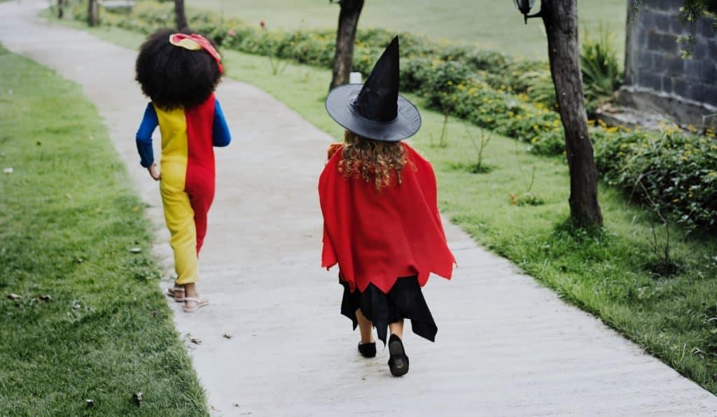 Na foto uma menina vestida de bruxinha e a outra de palhaço correndo.