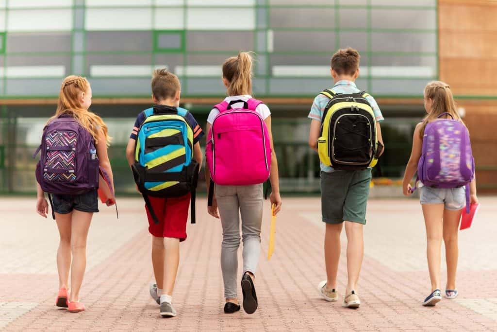 Imagem de crianças carregando mochilas nas costas.