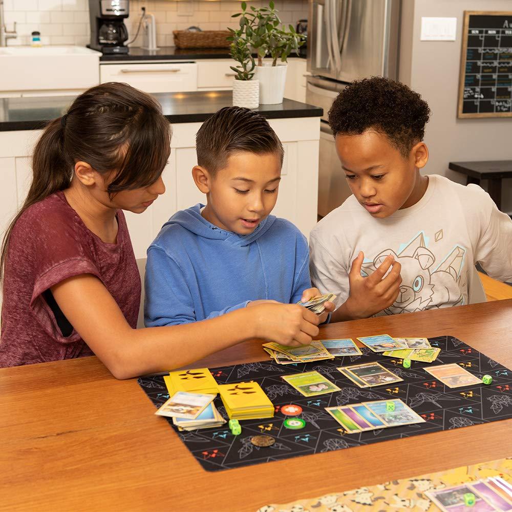 Três crianças, uma menina e dois meninos, estão sentados à mesa, em uma cozinha, brincando com o jogo de cartas Pokémon.