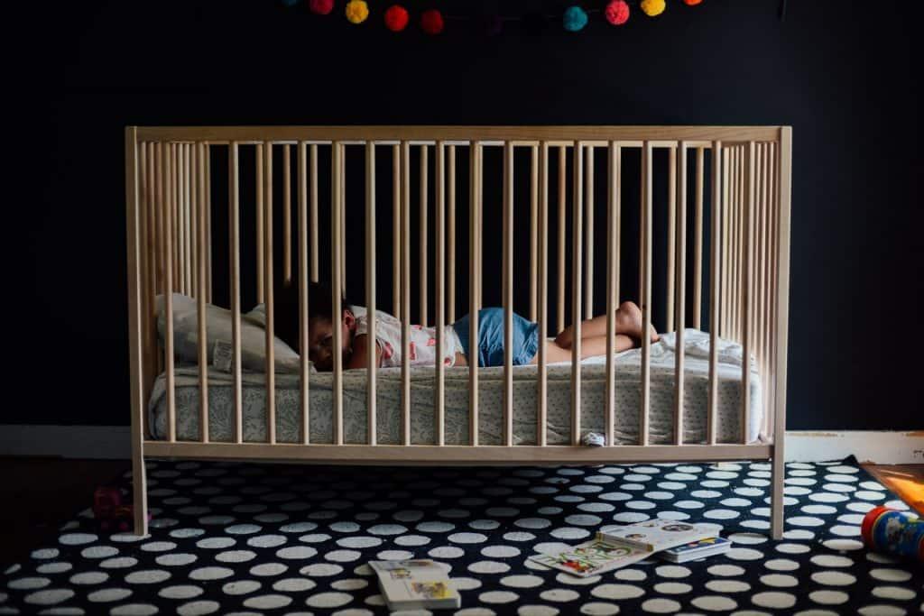 Foto mostra um bebê maior deitado de bruços em um berço que fica em um quarto com parede e tapete escuros.