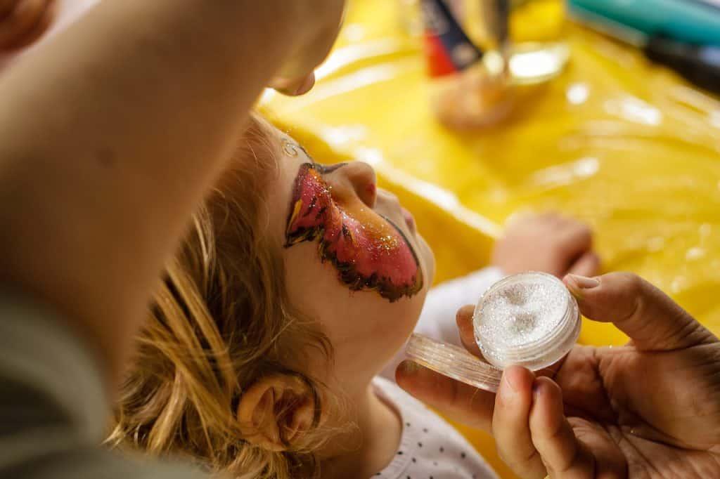 Imagem de pessoa fazendo maquiagem em criança e utilizando glitter.