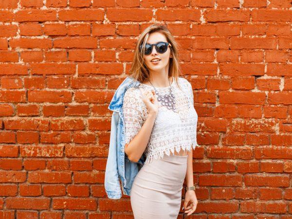 Na foto uma mulher em frente a uma parede de tijolos usando blusa saia e segurando uma jaqueta jeans.