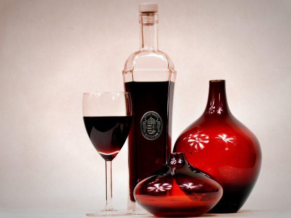 Taça de vinho e decantadores de diversos tamanhos e cores.