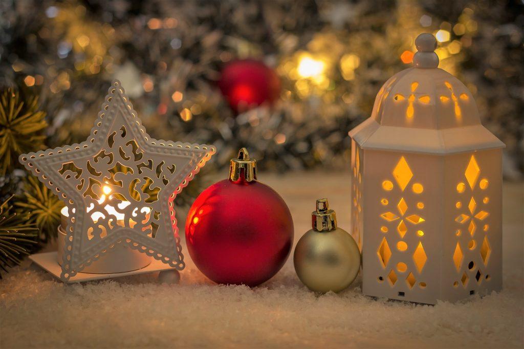 Velas e enfeites de natal em frente a uma frente a uma árvore de Natal.