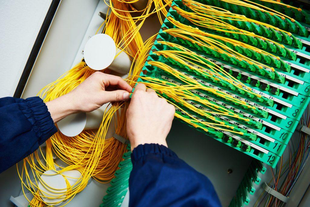 Pessoa mexendo em emaranhado de cabos.