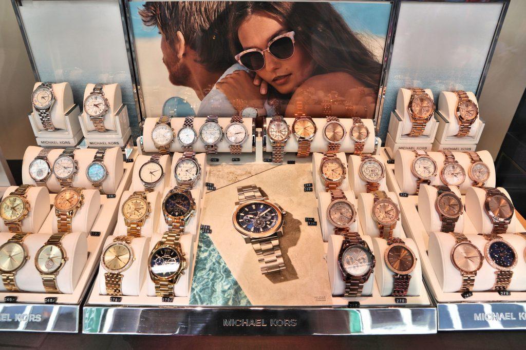 Imagem mostra uma vitrine de uma loja Michael Kors com diversos relógios.