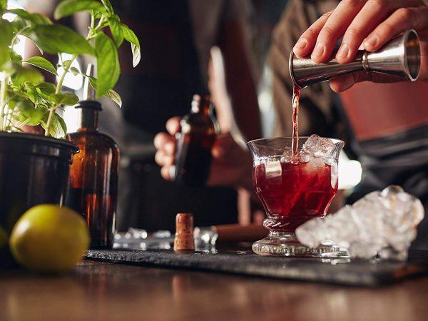 Uma pessoa vira um dosador que derrama uma bebida dentro de um copo de vidro cheio de gelo.